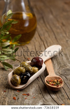 Mix of olives with jug of olive oil and spoon of spices on old wooden table