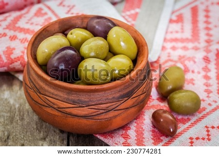 mix of organic olives in a bowl on a wooden background