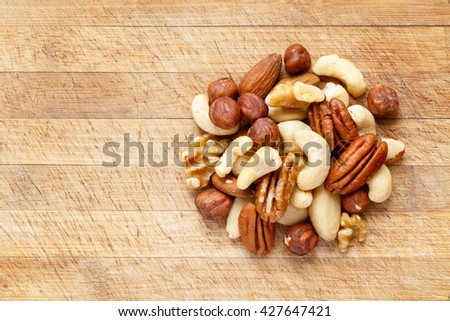 Mix of raw nuts on wooden cutting board