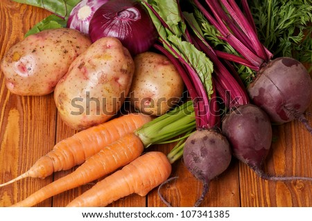 Mix of Raw Organic Farmer's Potato, Carrot, Red Onion and Beet on wooden background - stock photo