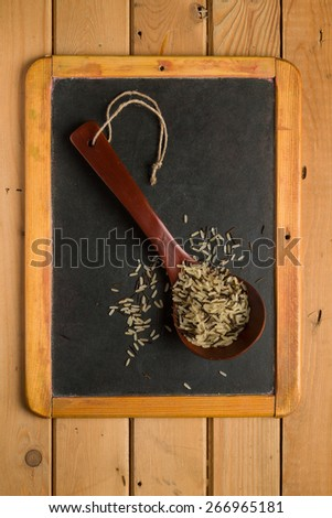 Mix of rice in a wooden spoon on a chalkboard - stock photo