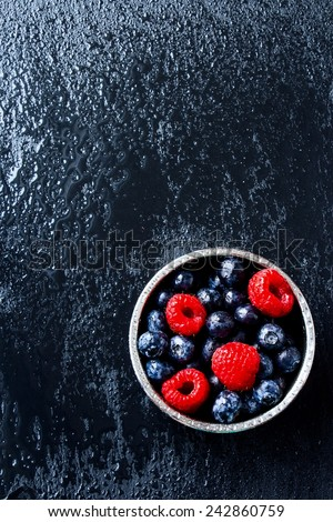 Mix of ripe berries in bowl on dark grey background. Top view. - stock photo