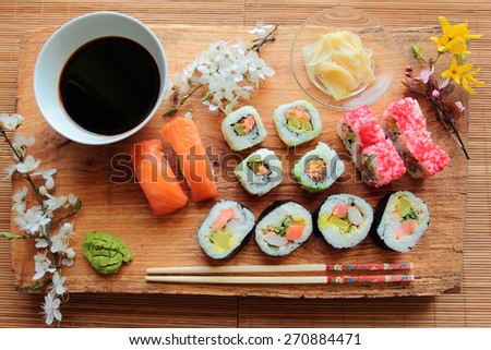 Mix of sushi rolls served on wooden desk with soy sauce - stock photo