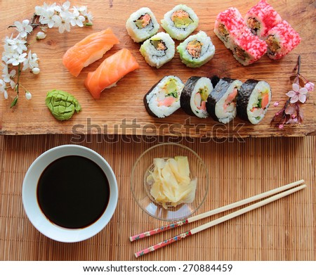 Mix of sushi rolls with soy sauce served on wooden desk - stock photo