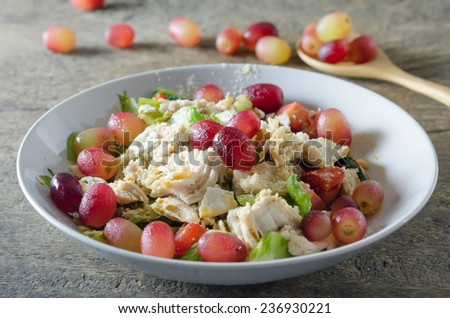 Mix salad with grapes and chicken on white dish - stock photo