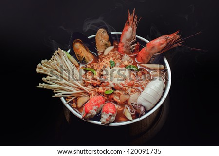 Mix Tom Yum seafood spicy soup traditional food cuisine in Thailand on black background - stock photo