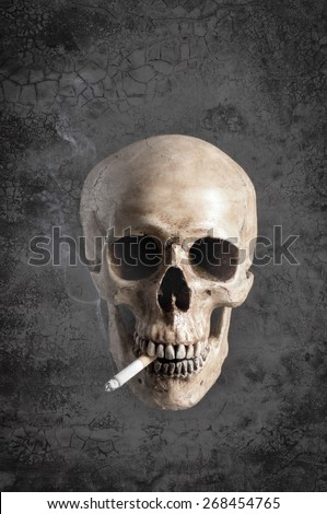 mix up of grunge background with human skull smoking the cigarette with some smoke in vintage color tone - stock photo