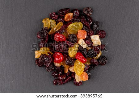 Mix variety of dried fruiton black dark stone background