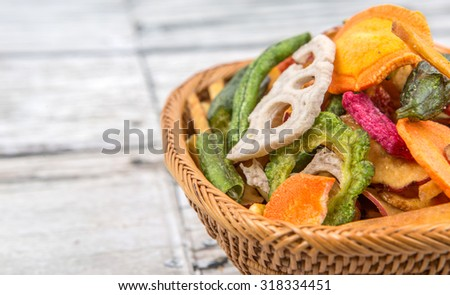 Mix vegetable chips in wicker bowl over wooden background