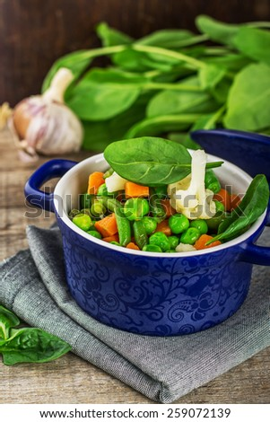 mix vegetables in a blue ceramic pot on a wooden background. selective Focus - stock photo