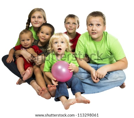 Mixed-age group of children sitting on something and watch with interest - stock photo