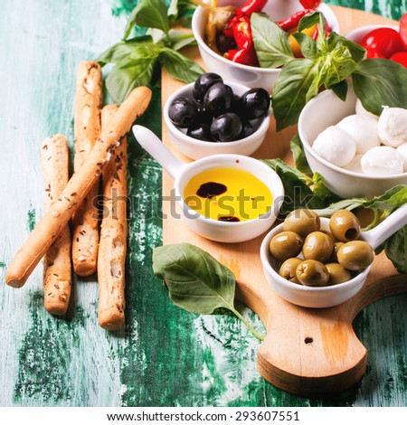Mixed antipasti olives and mozzarella served on wooden cutting board over green wooden table. Square image with selective focus. - stock photo