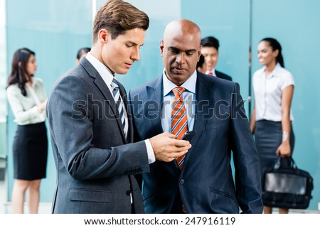 Mixed Asian and Caucasian business team meeting on terrace on front of their office - stock photo
