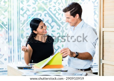 Mixed Asian Caucasian couple in furniture store or showroom choosing color and material for furnishing - stock photo