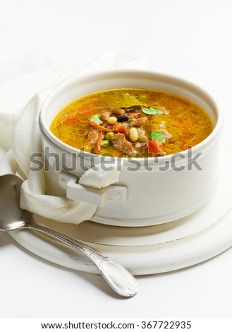 Mixed bean soup with pork meat, tomato and herbs - stock photo