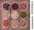 Mixed beans , lentils and nuts in the white bowl on brown cloth sack  background. mung bean, groundnut, soybean, red kidney bean , lotus seed ,almond,green bean,millet,cashew and brown pinto beans . - stock photo