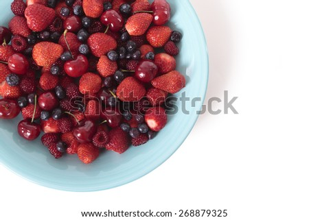 Mixed berries on blue bowl with white background - stock photo