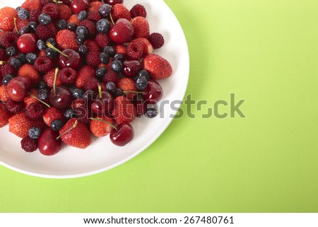 Mixed berries on white plate with copy space. Top view. - stock photo