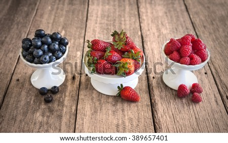 Mixed berries on white stands against wooden background - stock photo