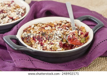 Mixed Berries, Plums & Apple Crumble - Cherry, blueberry, plum and apple filling topped with crumble made of pecan, almonds, pumpkin seeds and oats. - stock photo