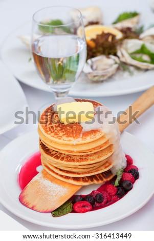 Mixed berry pancake on white plate. - stock photo