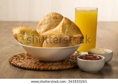 Mixed Brazilian deep fried chicken snack,, esfihas and pastry with juice and soda - popular at local parties.  - stock photo