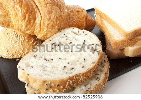 mixed bread, sesame bread, white bread and croissant on black tray.