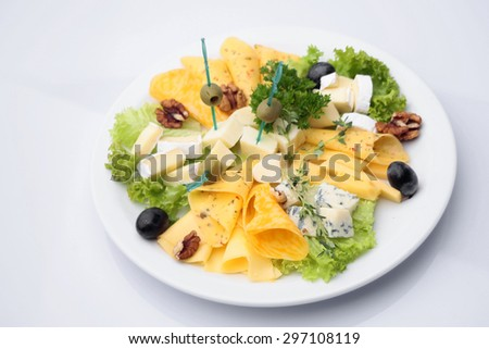 Mixed cheese diner platter from different varieties of cheese decorated with olives walnuts lettuce parsley isolated on white, horizontal picture - stock photo