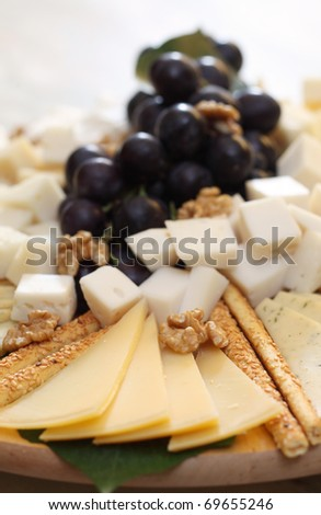 mixed cheese plate with some grape - stock photo