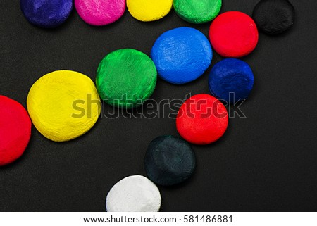 Mixed colors, different size circles, laid out on a dark background, close-up, top view