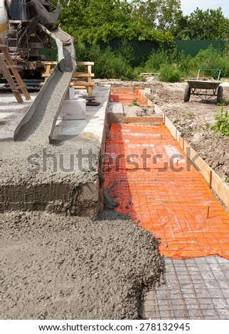 mixed concrete pouring at construction site - stock photo