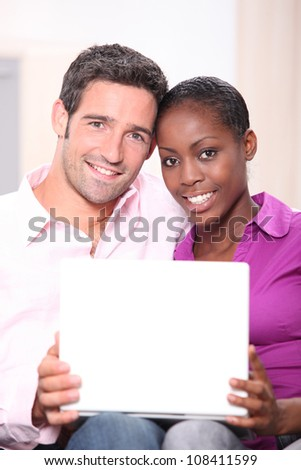mixed couple heads joined with laptop - stock photo
