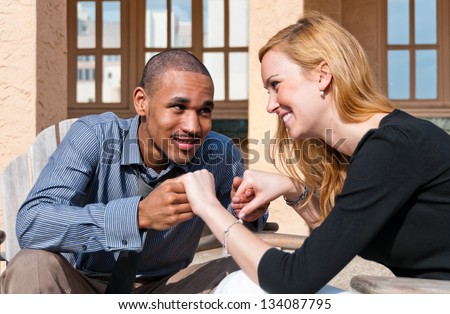 Mixed Couple holding hands, smiling, and locking eyes