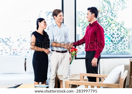 Mixed couple in furniture store with Asian shop assistant shaking hands sealing deal - stock photo