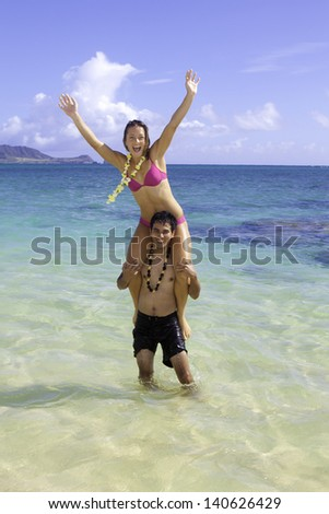 mixed couple playing at the beach in hawaii - stock photo
