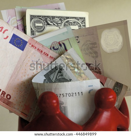 Mixed currency amid red figures. - stock photo