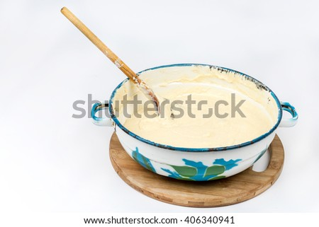 Mixed dough in the metal bowl isolated over white. - stock photo