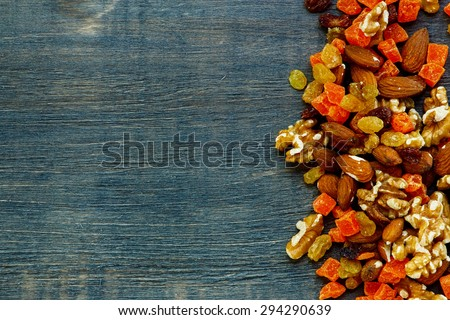 Mixed dried fruits and nuts on rustic wooden background with space for text. Healthy food. - stock photo