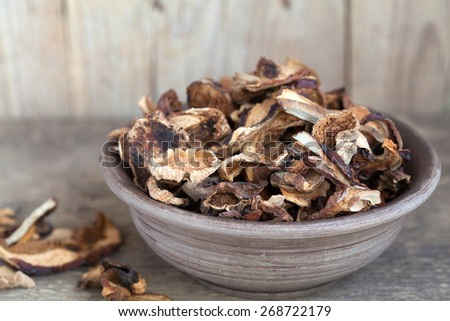 Mixed dried mushrooms (Porcini) in a bowl on the wooden table, selective focus - stock photo
