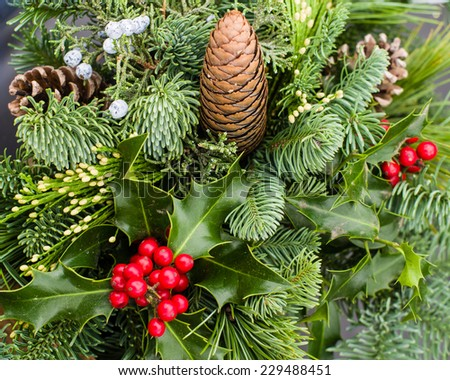 Mixed evergreen arrangement including pine cones holly and cedar - stock photo