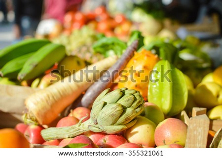 Mixed exotic fruits and vegetables on farmers market stall - stock photo