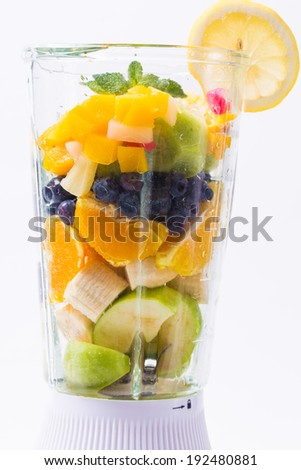 Mixed exotic fruits with leaf of mint in the blender ready to make cocktail - stock photo