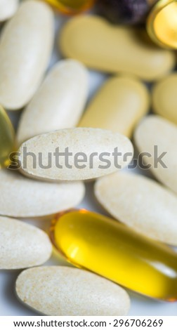 Mixed food supplement pills macro focused on vitamin C pills - stock photo