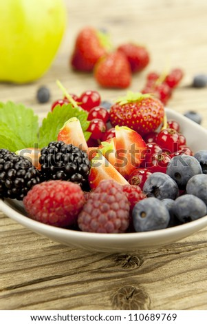 mixed fresh berries for dessert on wooden background in summer - stock photo