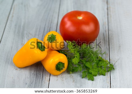 Mixed fresh colored vegetables, mini paprika, tomato and fresh herbs on a wooden background