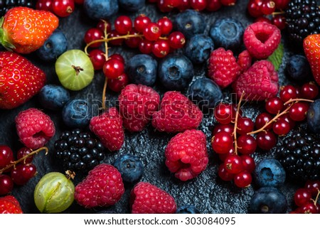 Mixed fresh ripe berries, food background from above
