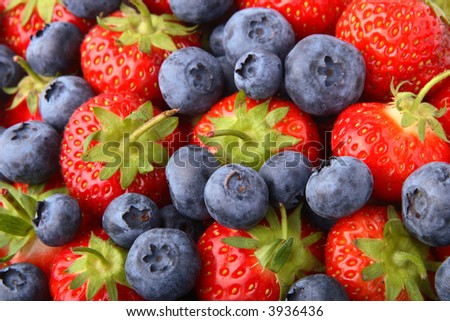Mixed fresh strawberries and blueberries filling frame.