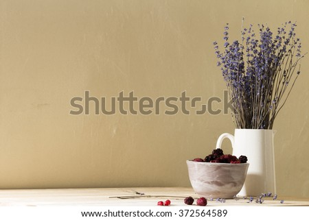 mixed frozen berries in a bowl with a jug of lavender