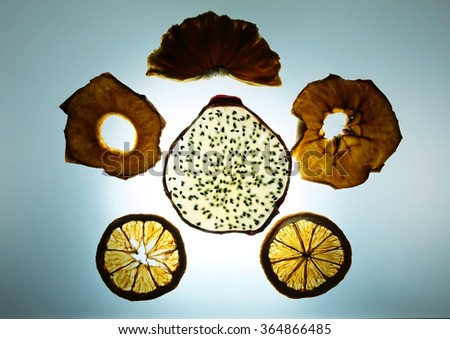 Mixed fruit dehydrating on tracing light board ; dragon fruit, grape fruit, apple, pineapple - stock photo