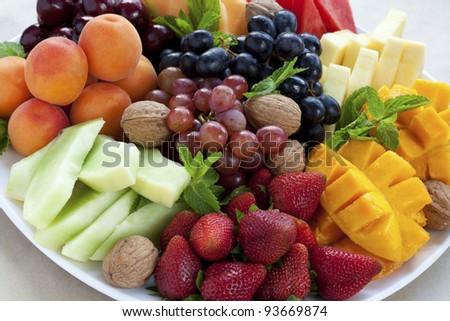 Mixed fruit platter with strawberries, mango, cantaloupe, grapes, apricots, walnuts and mint - stock photo